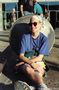 Me in the summer of 2000 at the Gay and Lesbian Association of Choruses Festival in San Jose, CA, sitting on the ground against a large concrete sphere, wearing a bandana, sunglasses, a blue shirt, freedom rings, multi-colored shorts, and tennis shoes, with a green jacket tied around my waist