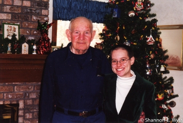 Me with my maternal grandfather in December 2000. We're standing in my parents' living room, in front of the Christmas tree. He has on a navy blue shirt and blue pants. I'm wearing a dark green suit jacket and white turtleneck.