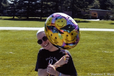 Me celebrating the end of graduate school, June 2001. I'm standing on a field of grass in a bandana, sunglasses, and Bread & Roses Feminist Singers t-shirt, carrying a mylar balloon festooned with smiley faces in graduation caps.