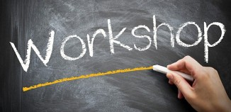 "A white hand draws a yellow line (with white chalk) underneath the word ""Workshop"" written in white chalk"